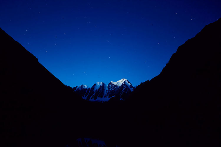 Low angle view of snowcapped mountains against blue sky at night