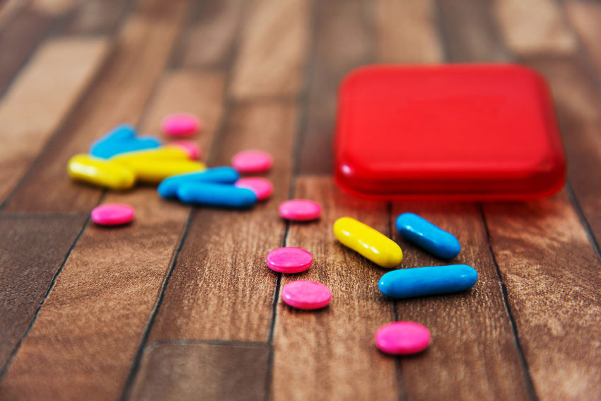 Multi Colored Pill Capsule Close-up No People Wood - Material Dose Indoors  Medicine Healthcare And Medicine Selective Focus Choice Large Group Of Objects Pink Color Still Life Studio Shot Variation Group Of Objects Table