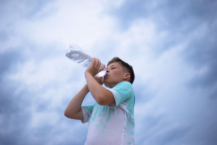 A boy against the sky drinks water from a plastic bottle. thirst. heat. cloudy sky.