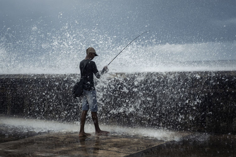 Man fishing while standing at sea shore