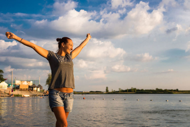 Smiling woman with arms outstretched walking at beach