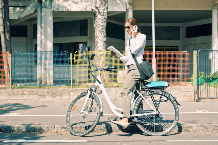 Side view of woman talking on smart phone while standing with bicycle on road