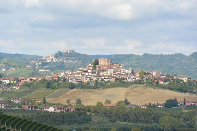 Scenic view of village in piedmont against cloudy sky