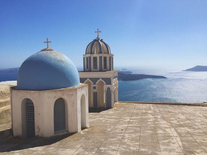 Church in Santorini by sea against clear blue sky