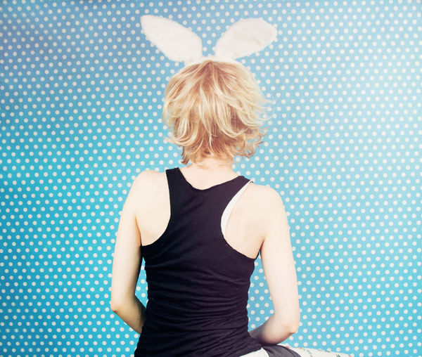 Rear View Of Woman Wearing Costume Rabbit Ears Against Blue Curtain
