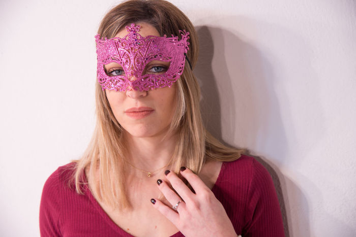 Blonde girl with carnival mask over white background. Masquerade. Portrait of Beautiful Blond Woman in a Carnival Mask. Masquerade. Girl. Beauty & Fashion Adult Adults Only Blond Hair Childhood Close-up Day Disguise Eye Mask Front View Headshot Indoors  Looking At Camera One Person People Portrait Real People White Background Young Adult