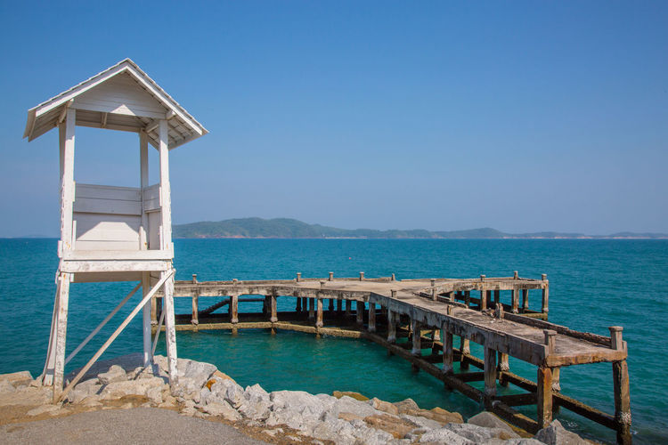 Lifeguard hut at beach against blue sky