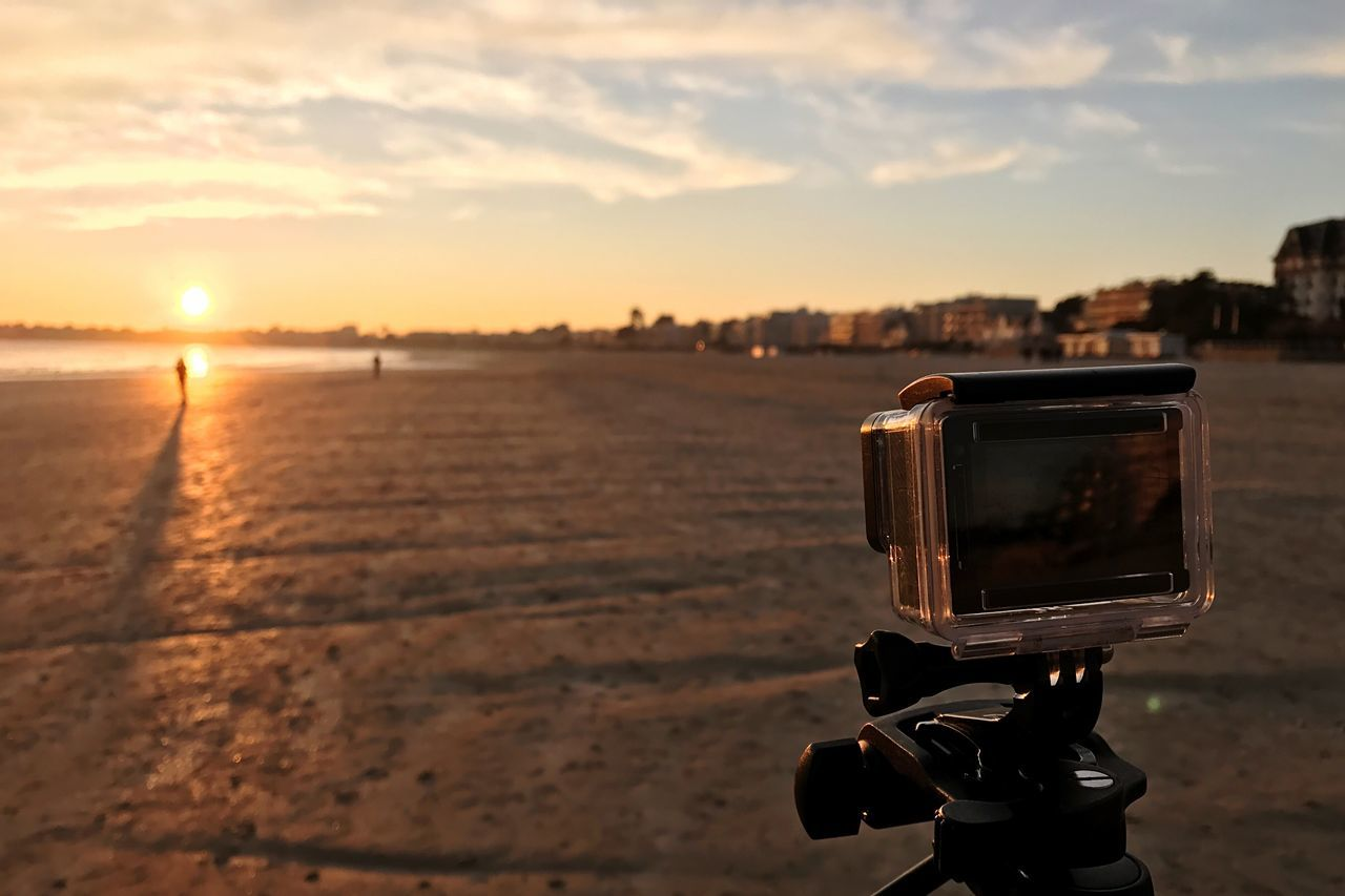 sunset, sky, technology, cloud - sky, photography themes, close-up, nature, focus on foreground, no people, beauty in nature, camera - photographic equipment, photographic equipment, outdoors, water, beach, land, modern, idyllic, city, tripod, digital camera