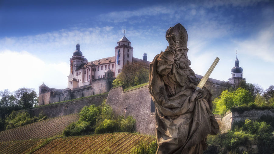 Saint Kilian and the Marienberg Fortress, Würzburg, Germany Marienberg Fortress St. Killian Würzburg Architecture Building Exterior Built Structure Cloud - Sky Day History Human Representation Low Angle View Male Likeness Nature No People Outdoors Place Of Worship Religion Sculpture Sky Spirituality Statue Travel Destinations Tree
