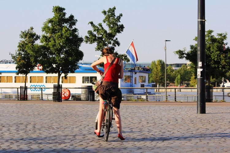Rear view of woman with french flag on bicycle at street