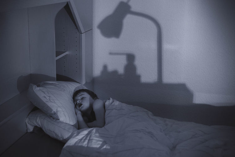 Woman lying on bed at home