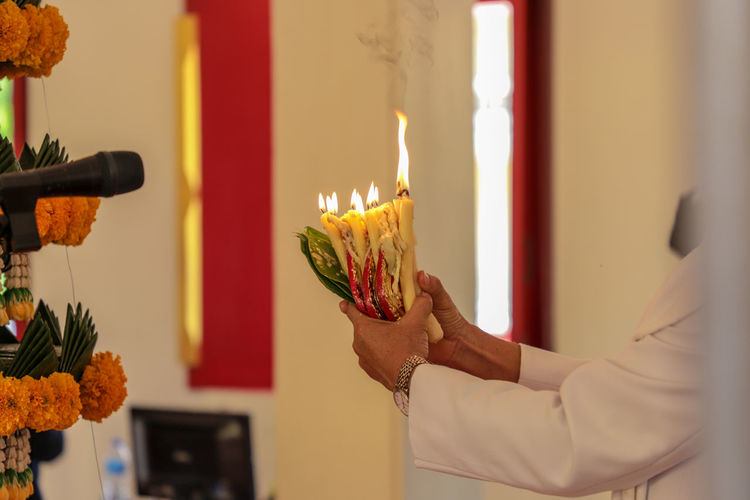 Worship. Thailand ASIA Southeast Asia Yasothon Ceremony Worship Focus On Foreground Heat - Temperature Event Celebration One Person Human Body Part Indoors  Hand Candle Human Hand Burning Fire Flame News