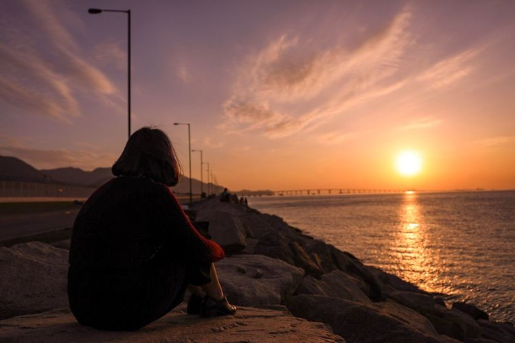 Side view of woman sitting at beach against sky during sunset
