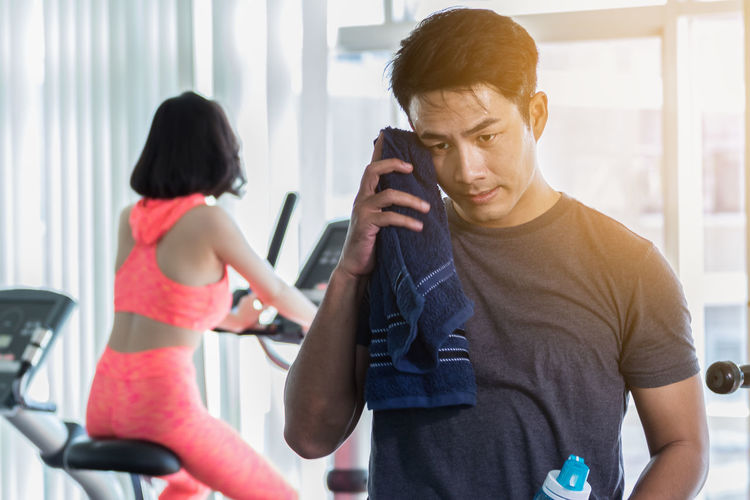Man wiping sweat with woman in background