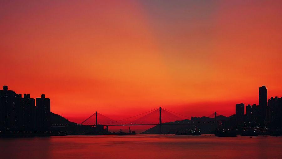 Silhouette Bridge Over River In City Against Orange Sky