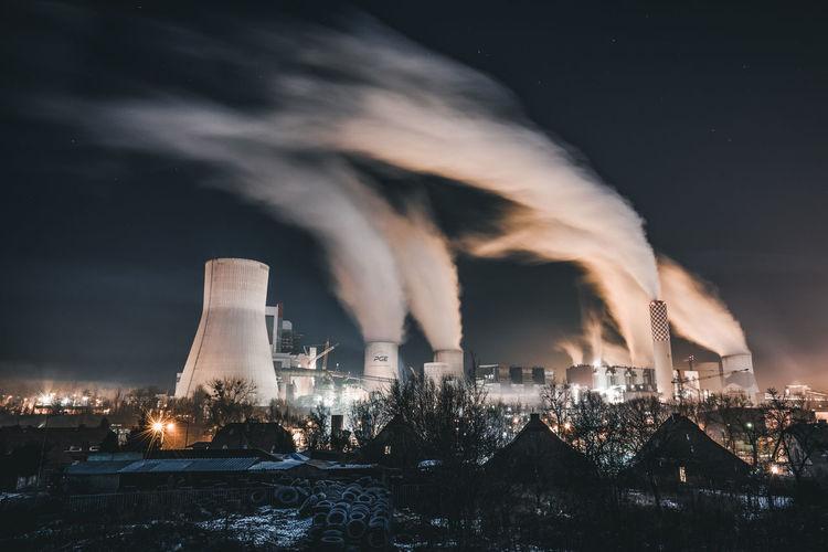 Smoke emitting from illuminated city against sky at night