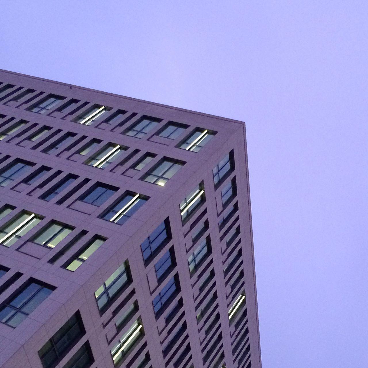 Purple tilt image of office building against sky at dusk