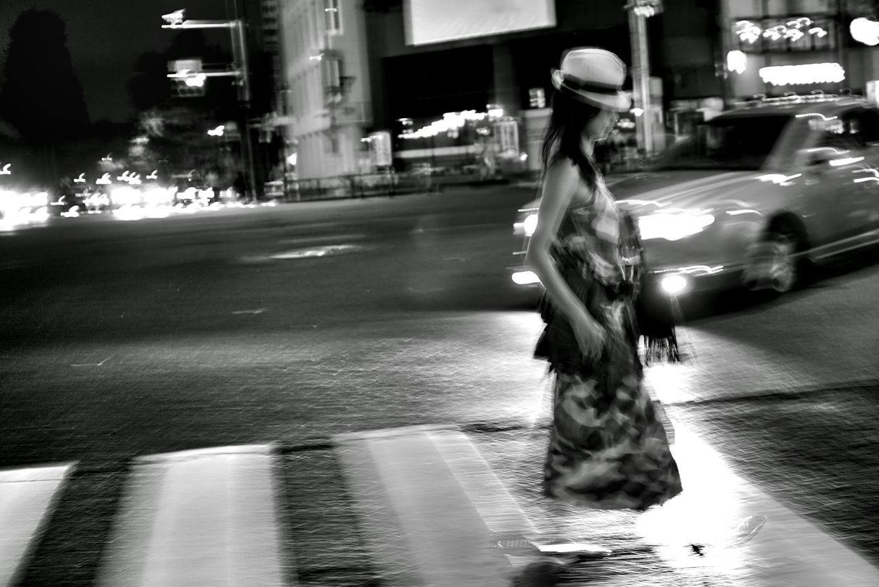 blurred motion, motion, street, real people, one person, full length, speed, transportation, long exposure, rear view, outdoors, night, women, lifestyles, riding, walking, road, city, bicycle, land vehicle, illuminated, architecture, building exterior, under, young adult, people