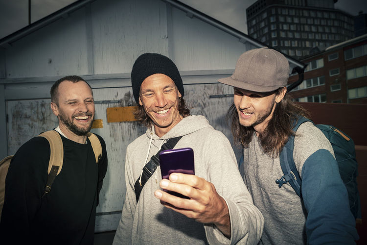 Portrait of happy friends standing on mobile phone