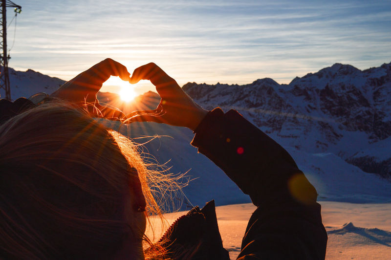Rear view of woman making heart shape against sun during sunset
