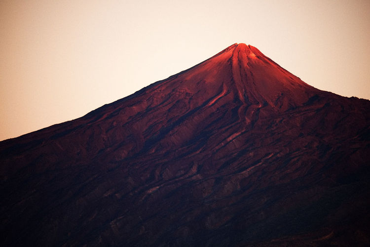 Low angle view of volcano against clear sky during sunset at teide national park