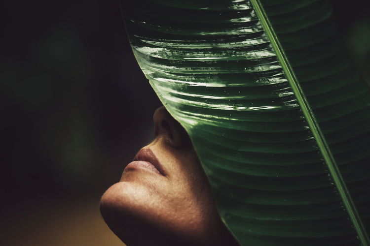 Close-up of young woman and a big leaf