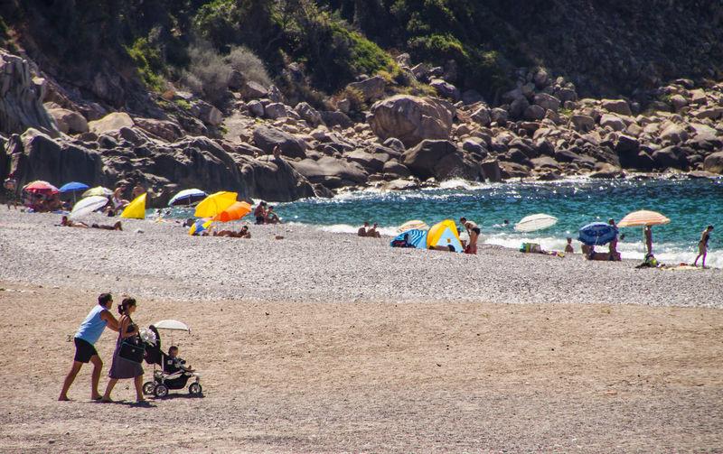 People Walking At Beach Against Rocks