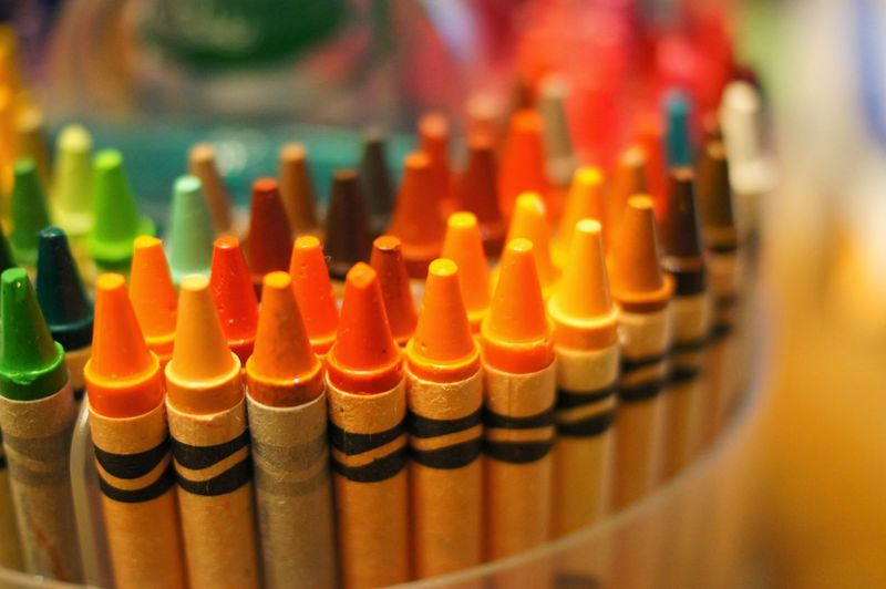 Close-up of multi colored crayons in container
