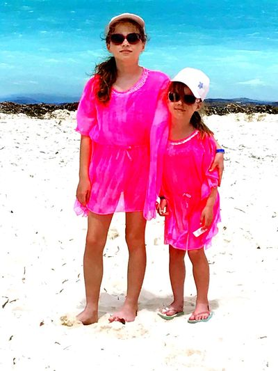 Neon Life Girls Beach Childhood Sisters Holiday Neon Pink Standing Sun Glasses Sun Hats White Sand Beach Blue Sea Lifestyles EyeEm Selects