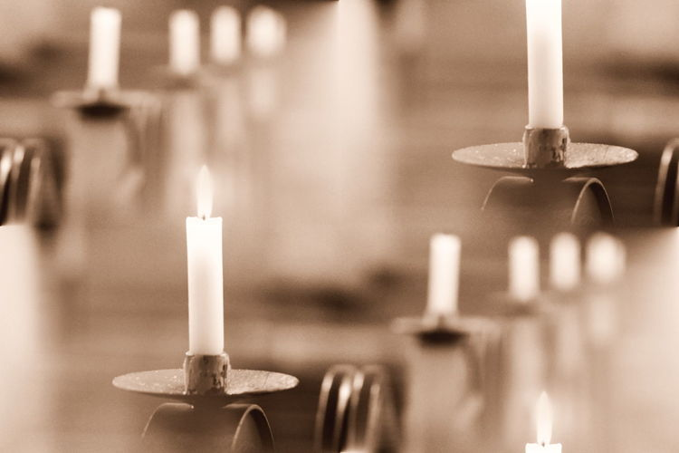 Close-up of lit candles on table in illuminated building