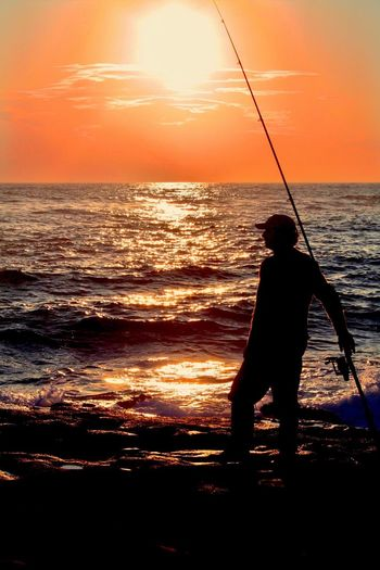Silhouette man fishing at beach against sunset sky