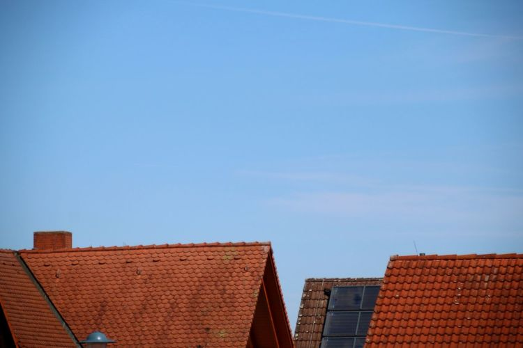 Low angle view of roofs against blue sky