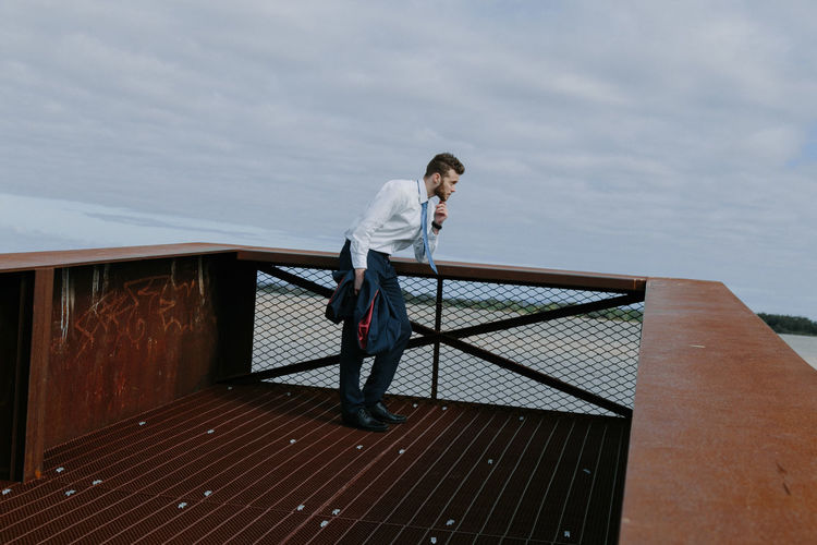 Young Man Looking Away While Standing By Railing Against Cloudy Sky