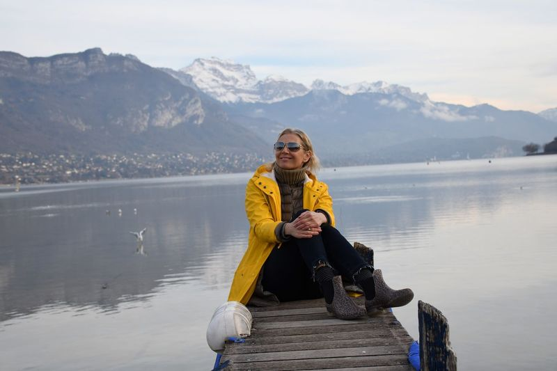 Woman sitting on pier over lake against mountain during winter