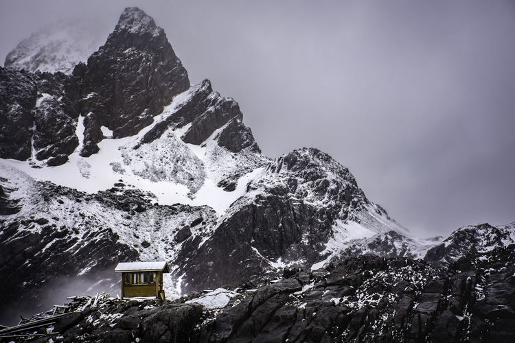 A little shed in front of jade dragon snow mountain peak,snowcapped mountain agains tge sky