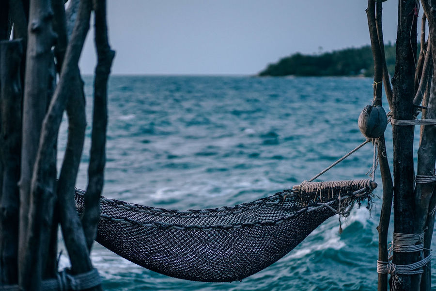 Brown net hammock hanging between the dry trees at the beach at Koh Raham. Photograph taken during dusk. The background is the sea waves splashing water and an island at horizon. Hanging Beauty In Nature Brown Clear Sky Day Dry Focus On Foreground Hammock Horizon Horizon Over Water Island Nature Net No People Outdoors Rope Scenics - Nature Sea Sky Tranquil Scene Tranquility Tree Tree Trunk Trunk Water