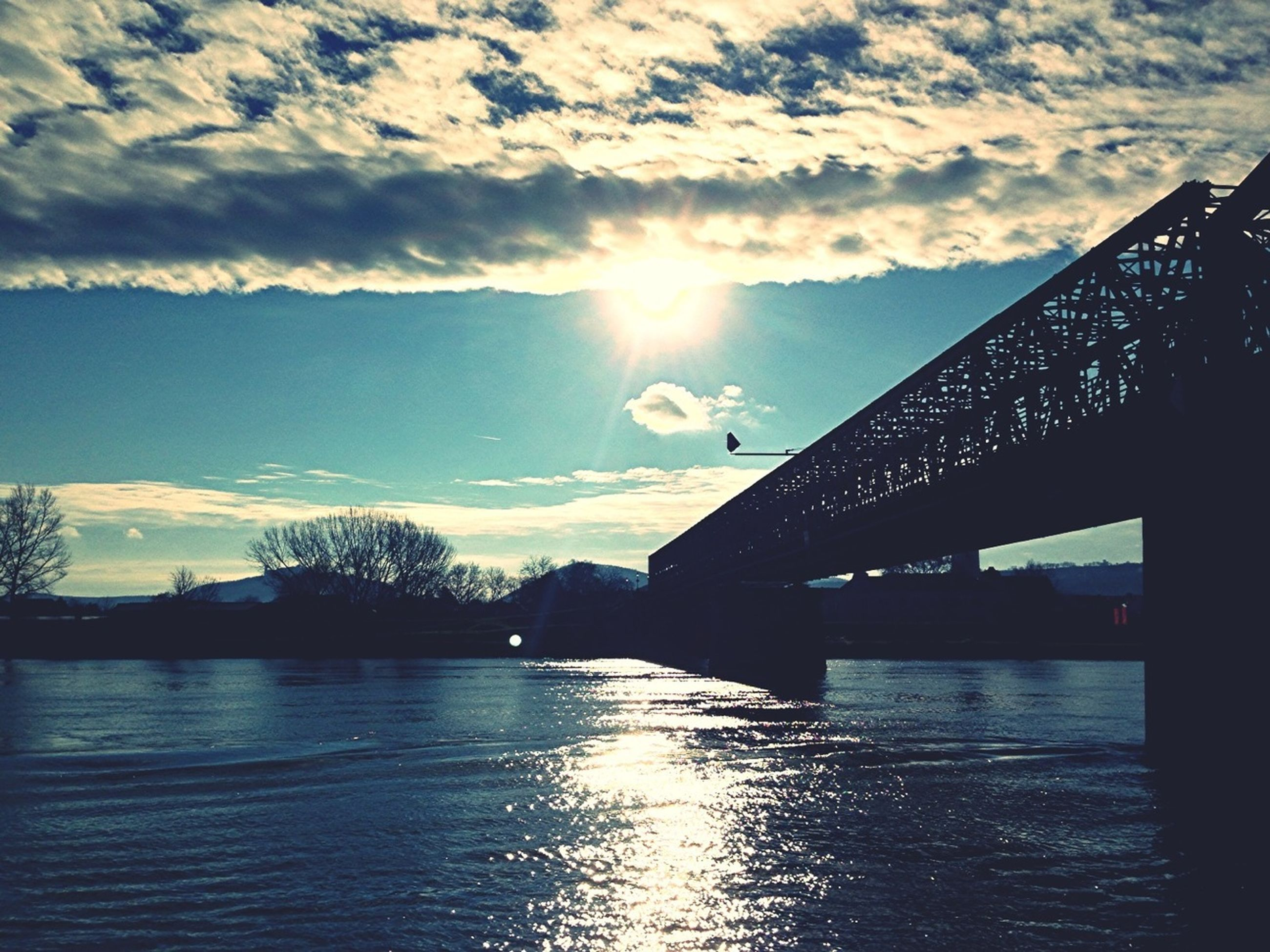 built structure, architecture, sun, sky, bridge - man made structure, water, river, building exterior, waterfront, connection, cloud - sky, sunbeam, sunlight, reflection, sunset, cloud, bridge, lens flare, silhouette, city