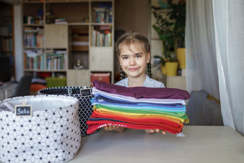 Portrait of smiling girl holding clothes at home