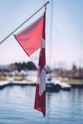 Close-up of canadian flag by lake on sunny day