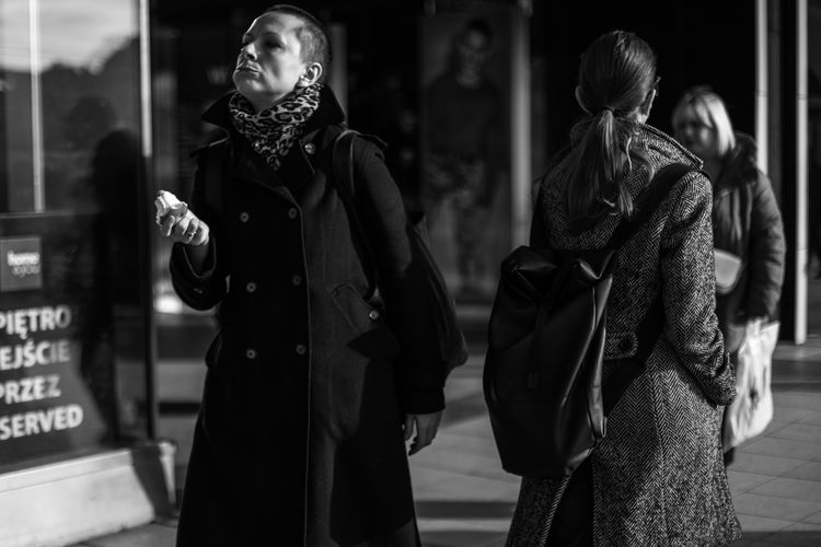 Young woman looking away while standing on street in city during winter