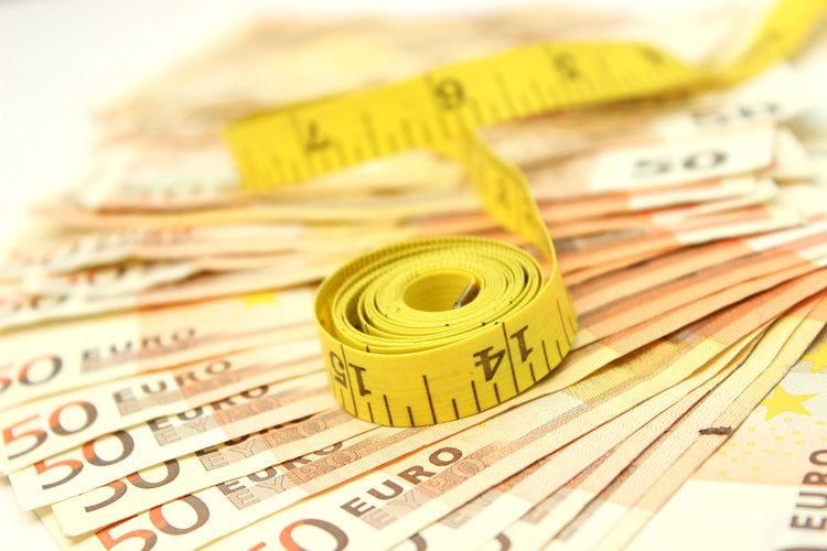Close-Up Of Tape Measure On Paper Currencies