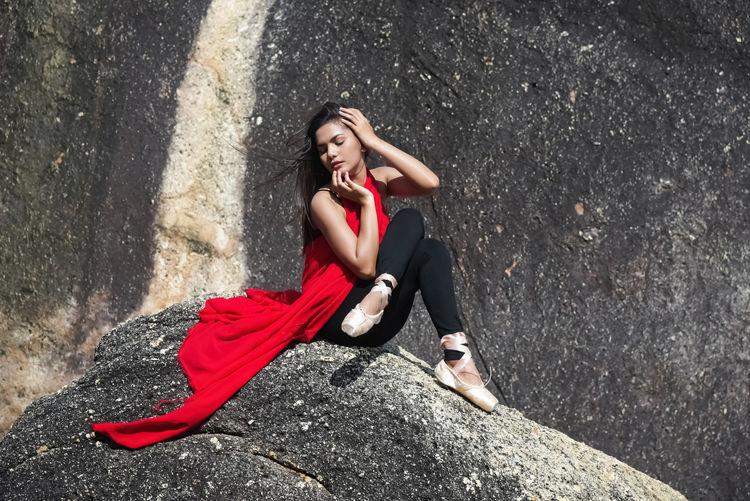 Full length of ballet dancer sitting on rock