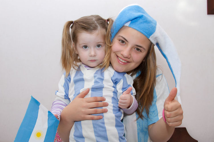 Portrait Of Sisters With Argentinian Flag Against Wall