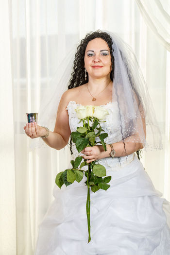 Young woman holding flower bouquet against white wall
