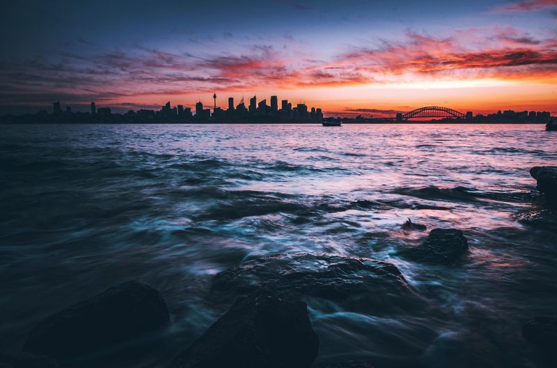 Scenic View Of Seascape By City During Sunset