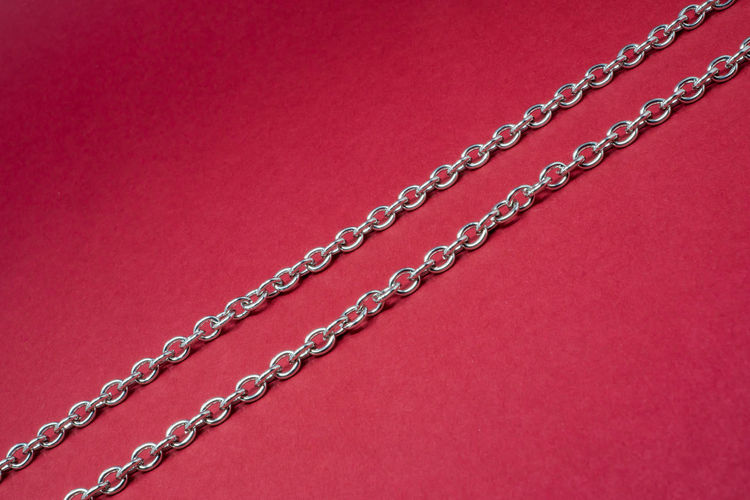 Low Angle View Of Chain On Red Background