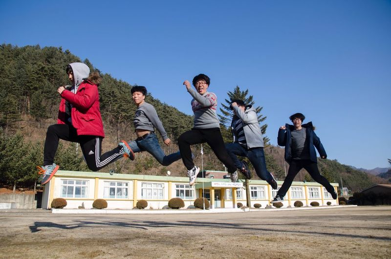 Tour Of Korea Clear Sky Leisure Activity Casual Clothing Friendship Motion Low Angle View Sport Men People Jumping School