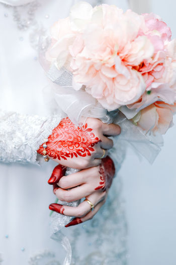 Beautiful henna on bride's hand One Person Real People Women Adult Human Hand Human Body Part Red Lifestyles Hand White Color Holding Finger Flowering Plant Flower Plant Freshness Beauty In Nature Close-up Nature Leisure Activity Flower Head