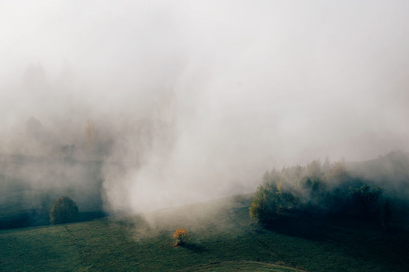 Scenic view of landscape during foggy weather against sky