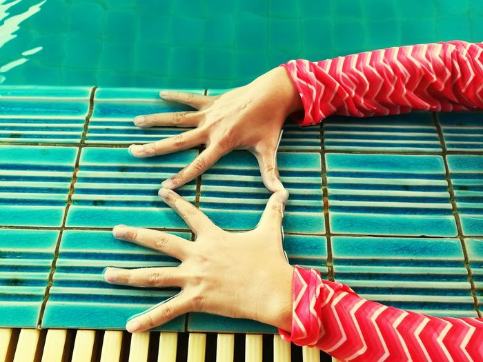 Cropped Hands Of Woman Making Finger Frame At Poolside